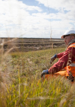 Photo of worker sitting in grass at Wallasea Island with an excavator in the background