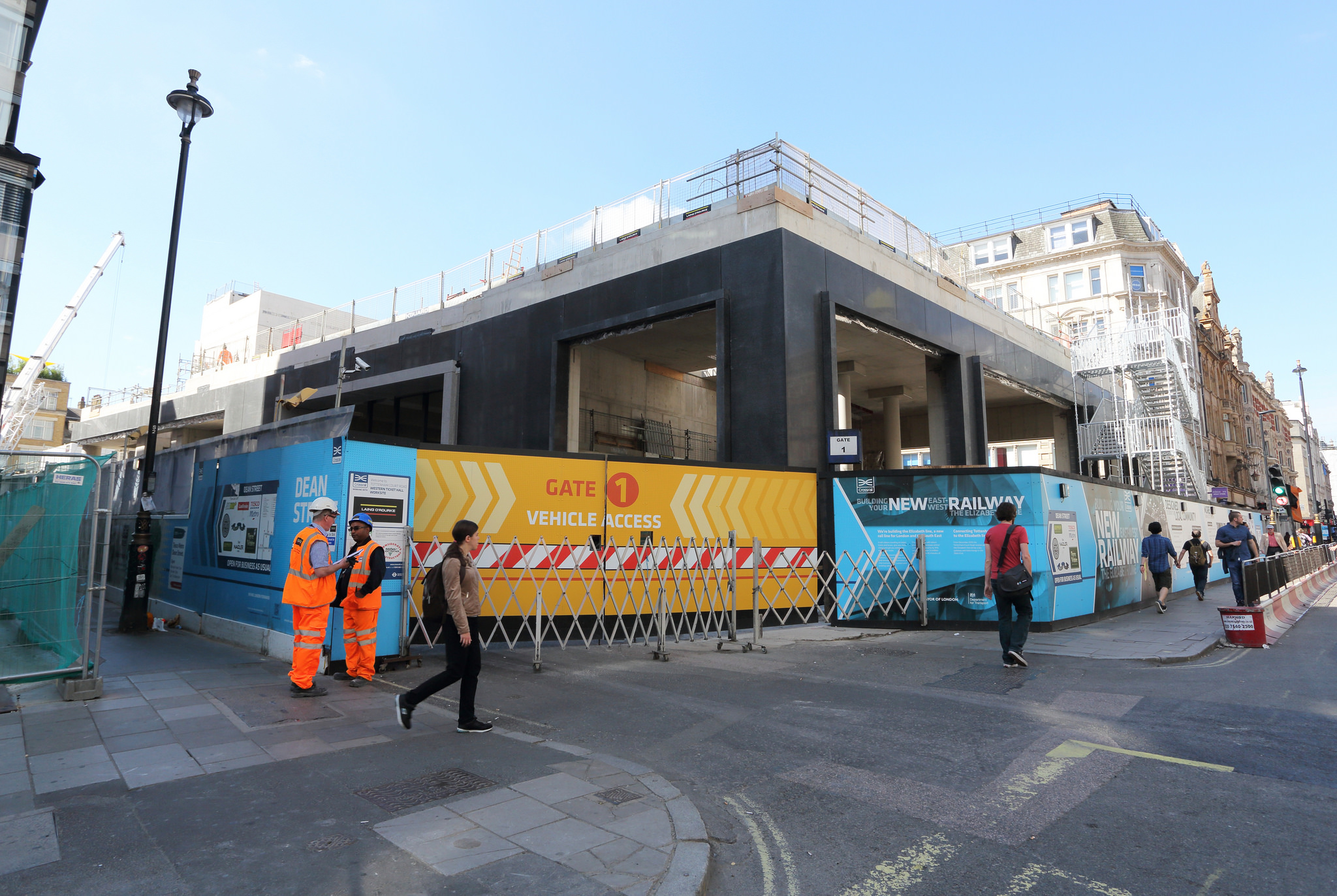 Photo of Dean Street worksite from Oxford Street showing site hoardings including vehicle access gate