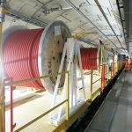 A construction train in a tunnel, carrying large reels of red cable